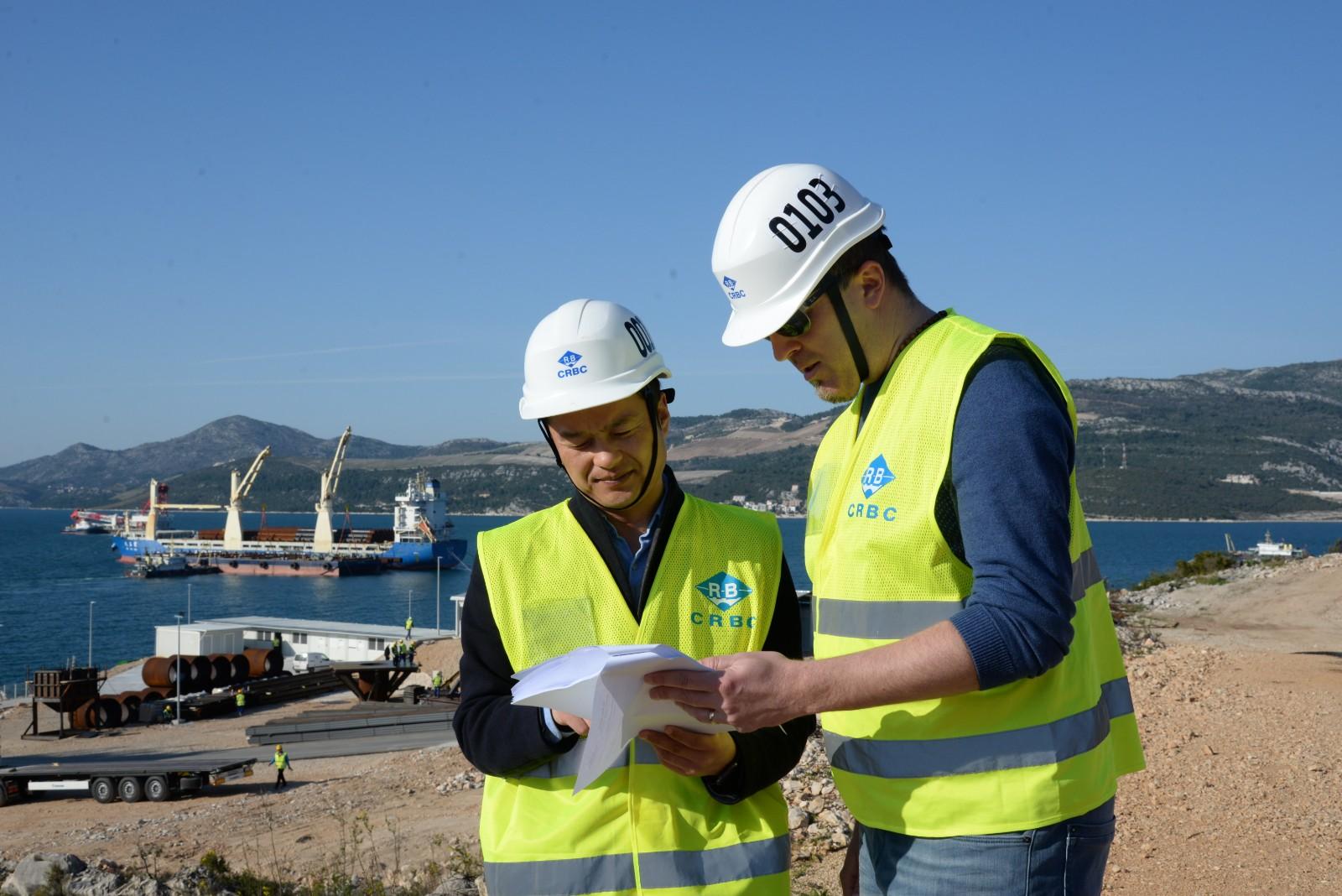 3月21日,中国路桥公司工程师张飞(左)和克罗地亚籍同事伊维察·格拉尼奇在克罗地亚佩列沙茨半岛查看图纸。今年1月,克罗地亚总理普连科维奇视察由中企承建的克罗地亚佩列沙茨跨海大桥及其连接线一期工程项目工地时,对中国企业的施工进度表示赞赏,并指出佩列沙茨大桥意义重大,体现克中两国良好合作关系。